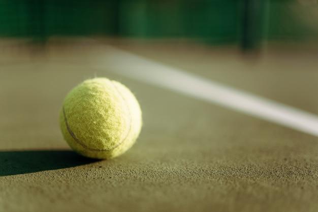 Palla da tennis sul primo piano di copertura del suolo, concetto di gioco.