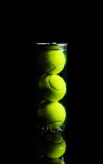 Palla da tennis isolata sul nero con illuminazione drammatica