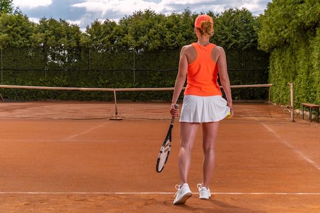 Palla da tennis in mano di una donna in una gonna su un campo da tennis.