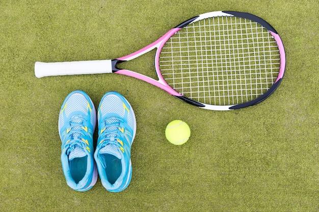 Set di attrezzature da tennis di racchetta da tennis, palla e scarpe da ginnastica femminili sul campo in erba verde