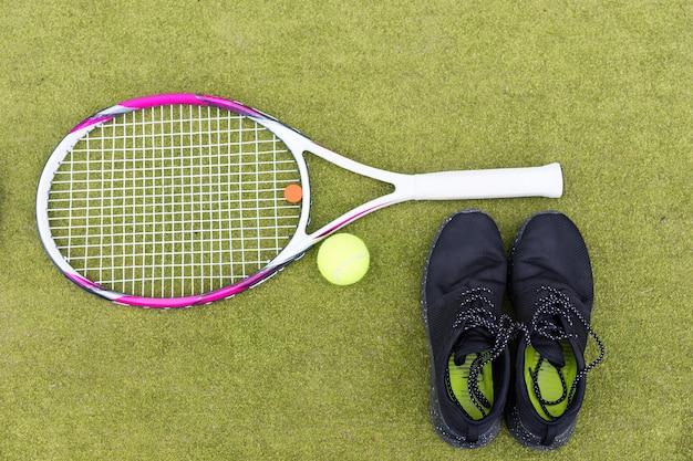 Set di attrezzature da tennis di racchetta da tennis, palla e scarpe da ginnastica maschile sul campo in erba verde