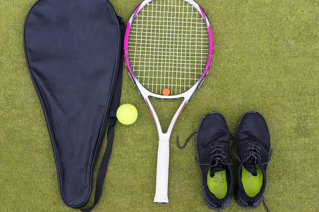 Attrezzatura da tennis set di racchetta da tennis con copertura, palla e scarpe da ginnastica maschile su campo in erba verde