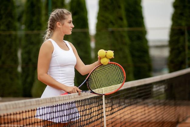 Giocatore di tennis. ragazza felice, in piedi con la racchetta e la pallina da tennis sul campo, vicino alla rete