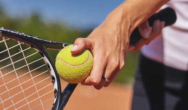 Un giocatore di tennis che tiene la racchetta e la palla nelle mani