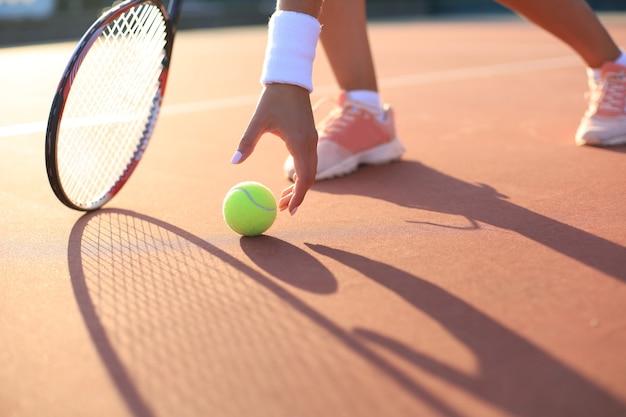 Il tennista solleva una pallina da tennis dal campo in terra battuta durante il gioco.