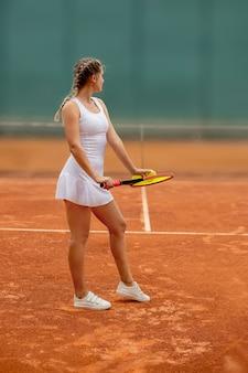 Giocatore di tennis in abiti sportivi che si prepara a servire la pallina da tennis
