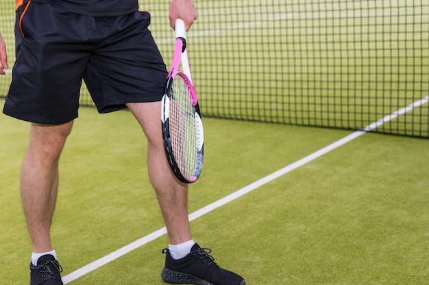Giocatore di tennis che indossa un abbigliamento sportivo in fase di riscaldamento prima della partita di tennis su un campo all'aperto in estate o in primavera