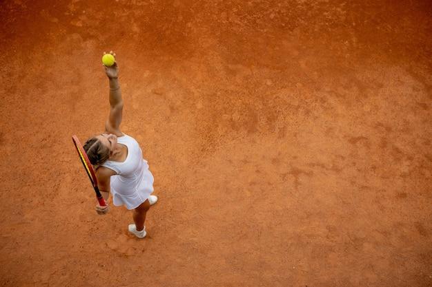 Giocatore di tennis in abiti sportivi bianchi si prepara a servire la pallina da tennis, si allena prima della partita. vista dall'alto