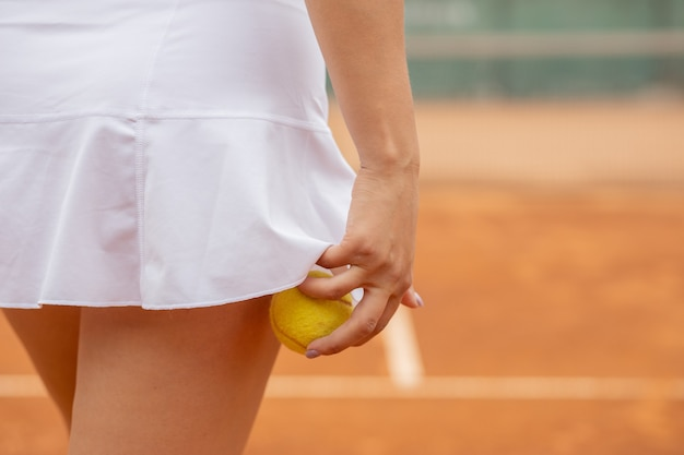 Giocatore di tennis in abiti sportivi bianchi si prepara a servire la pallina da tennis, si allena prima della partita.