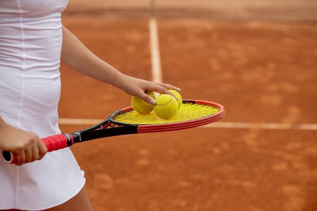 Giocatore di tennis in abiti sportivi bianchi che si prepara a servire l'allenamento con la pallina da tennis prima della partita