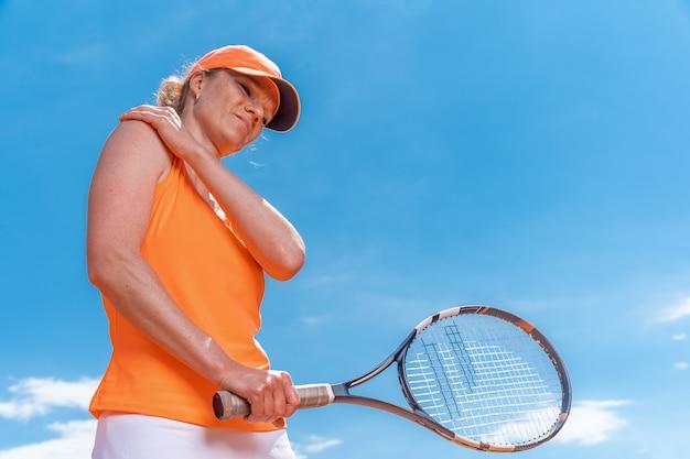 Tennista donna con infortunio che tiene la racchetta su un campo