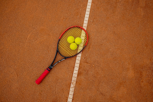Racchetta da tennis e palline gialle su un campo rosso mattone.