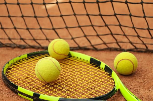 Racchetta da tennis con palline da tennis su campo in terra battuta