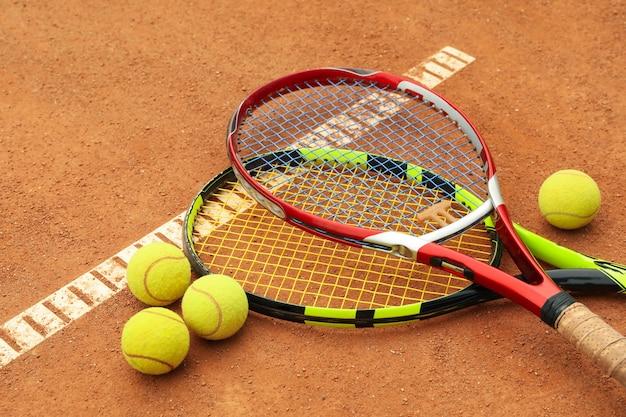 Racchette da tennis con palline da tennis su campo in terra battuta