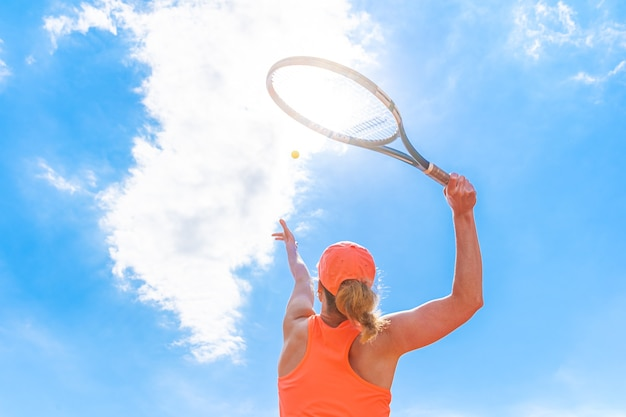 Servizio di tennis da una giovane donna in campo. vista dal basso