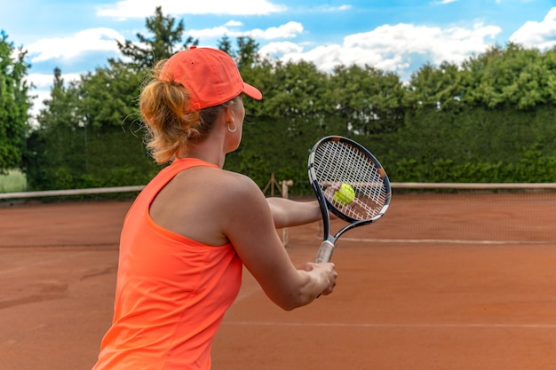 Servizio di tennis da una giovane donna in campo.