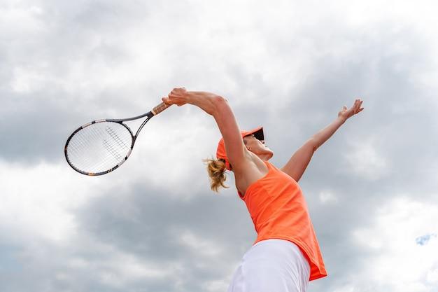 Servizio di tennis da una giovane donna in un torneo