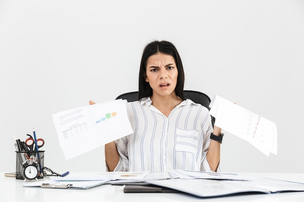 Tesa bruna imprenditrice urlando e sottolineando mentre si lavora con documenti cartacei in ufficio isolato sopra il muro bianco