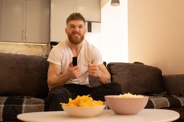 L'uomo teso si siede sul divano e guarda la tv o un film. giovane ragazzo barbuto europeo che tiene il telecomando. ciotole con patatine e popcorn sul tavolo. concetto di riposo a casa. interno del monolocale