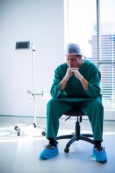 Chirurgo teso che si siede su una sedia