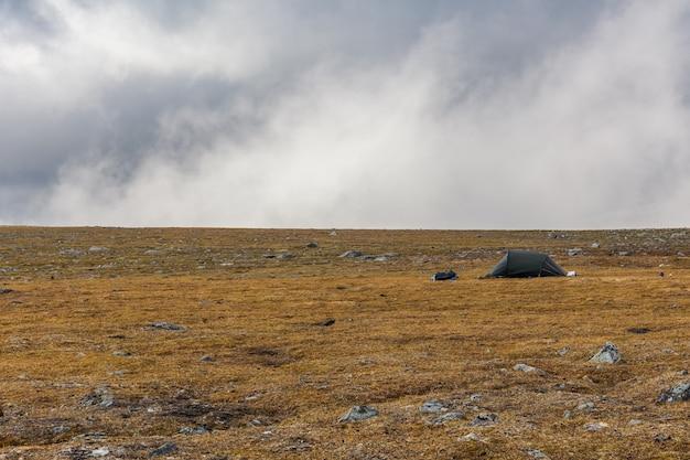 Tenda in autunno alpinisti sotto il cielo drammatico pieno di nuvole pesanti. tenda solitaria in montagna.