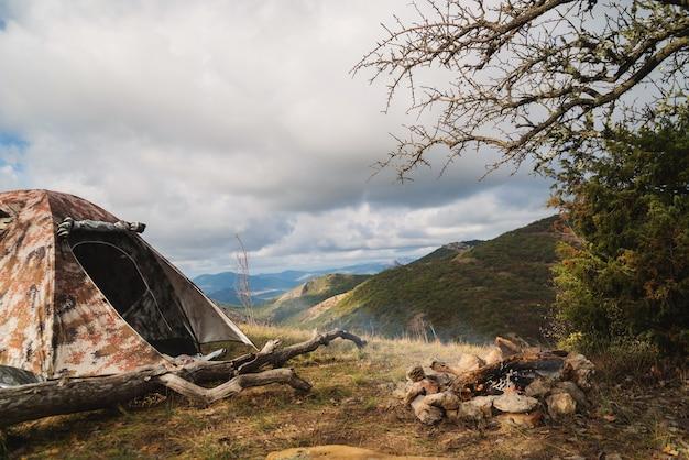 Tenda in montagna vicino a un falò durante un'escursione in un campo turistico, attività, riposo, relax, silenzio