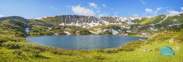Tenda sulla riva di un pittoresco lago di montagna