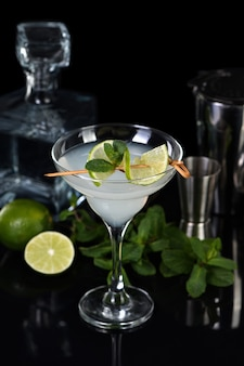 Tequila, liquore agli agrumi, succo di lime: questo è un cocktail margarita. un bicchiere di lime con un rametto di menta decora un bicchiere. cibo lunatico scuro