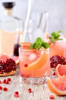 Cocktail di tequila con succo di melograno e pompelmo, colorato con l'aroma di un rametto di menta fresca