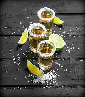 Tequila in un bicchierino con sale e fettine di lime fresco. sulla superficie rustica nera