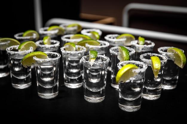 Colpi di tequila con lime e sale marino sulla tavola nera