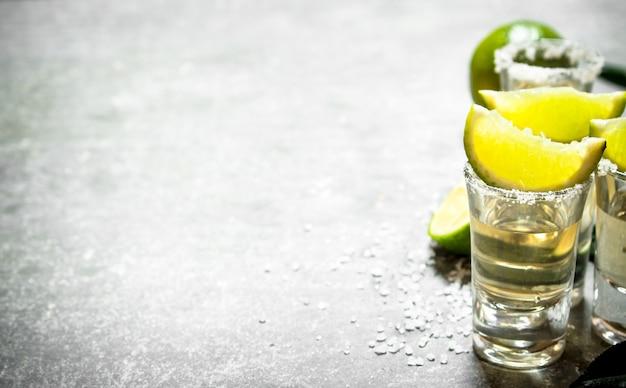 Tequila con lime e sale. sul tavolo di pietra.