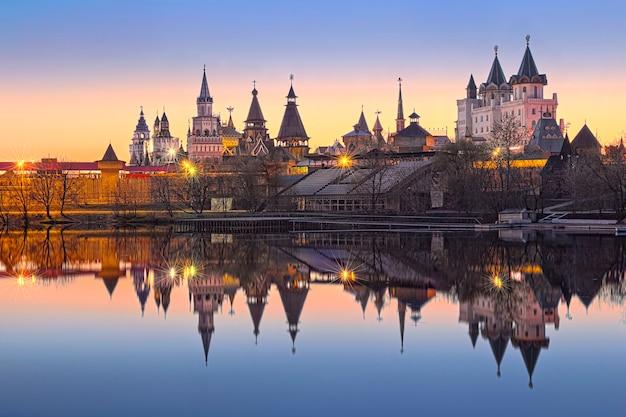 Teremki del cremlino izmailovsky a izmailovo a mosca con riflesso nell'acqua di uno stagno alla luce delle luci della sera