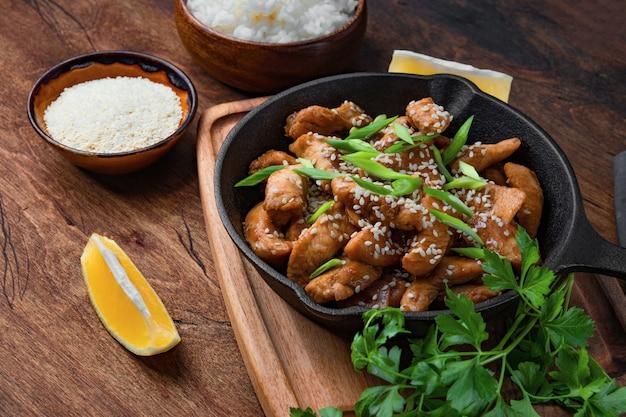 Teriyaki petto di pollo in padella con riso e semi di sesamo vista dall'alto, cibo asiatico tradizionale. foto di alta qualità