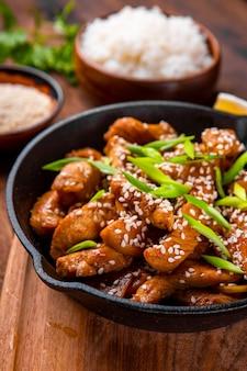 Petto di pollo teriyaki in una padella con il primo piano di semi di sesamo, cibo asiatico tradizionale