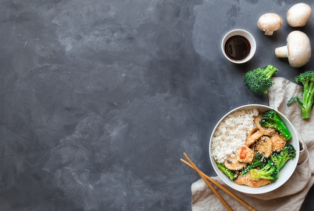 Pollo teriyaki, broccoli e funghi saltati in padella con riso bianco in una ciotola su sfondo grigio cemento. cucina asiatica. vista dall'alto con spazio per il testo.