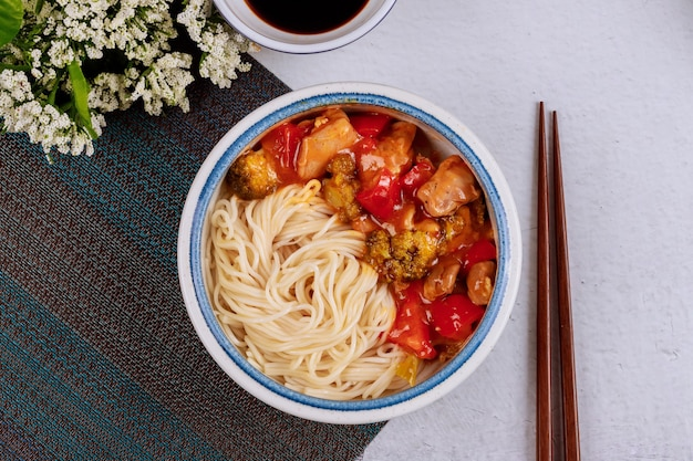 Pollo teriyaki con peperoni, broccoli e noodles in una ciotola con le bacchette. vista dall'alto.