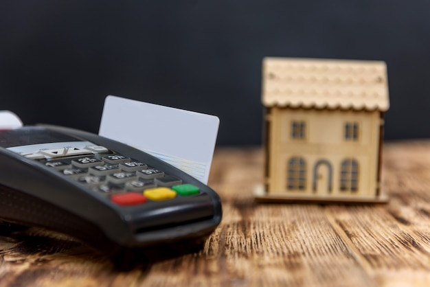 Terminale con carta di credito e modello casa in legno