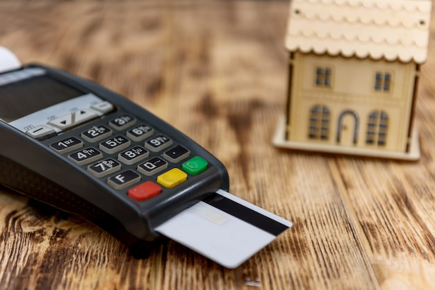 Terminale con carta di credito e modello di casa in legno