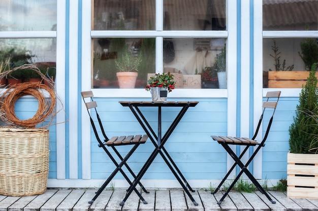 Terrazza con cesti di vimini e piante verdi in vaso sul portico di casa. tavolo e sedie in legno sulla veranda della casa. decorazioni per la casa all'aperto