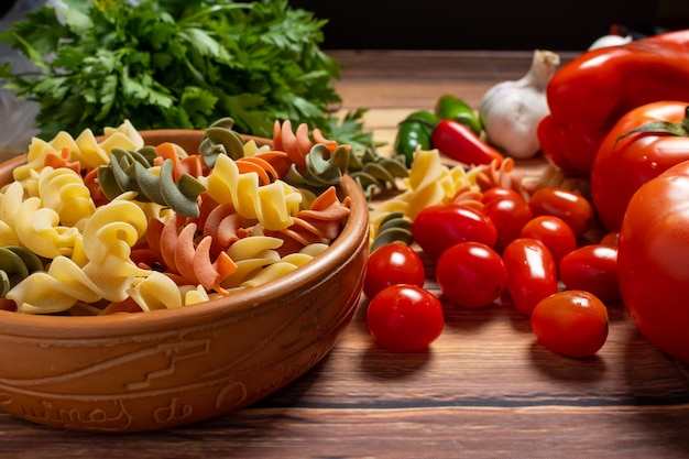 Ciotola in terracotta con fusilli tricolori e pomodorini tondi, peperoncino, aglio e prezzemolo.