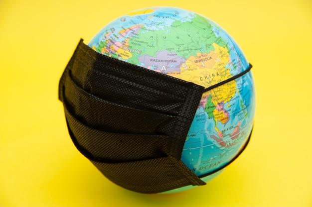 Modello di globo terrestre con mascherina chirurgica nera isolata su giallo