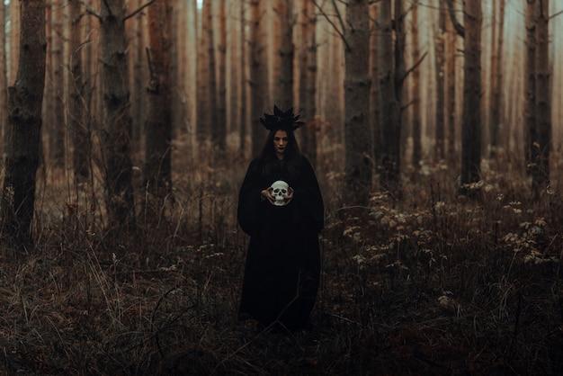Terribile strega tiene il teschio di un uomo morto tra le mani in una foresta oscura