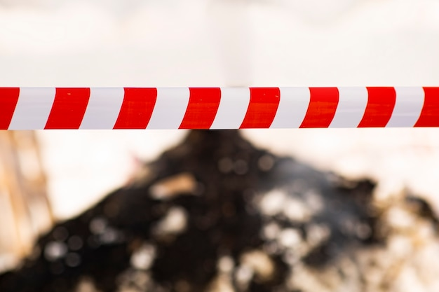 Un'immagine terribilmente inquietante della fine di un incendio ardente con un nastro di avvertimento: mezzi di estinzione e protezione antincendio