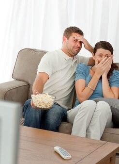 Coppia terrorizzata guardando un film horror
