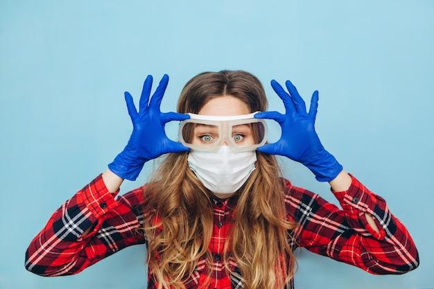 Ragazza terrorizzata in occhiali protettivi, maschera medica e guanti blu su sfondo blu. ritratto di close-up di una donna in una maschera trasparente. modo di proteggere dal coronavirus. covid-2019, pandemic 2020