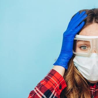 Donna terrorizzata in occhiali protettivi, mascherina medica e guanti blu. ritratto di close-up di una donna in una maschera trasparente. modo di proteggere dal coronavirus. covid-2019