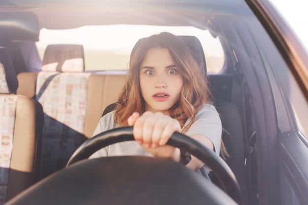 La giovane donna carina terrorizzata guarda con espressione depressa spaventata davanti mentre guida l'auto, ha una collisione con altri mezzi di trasporto o un incidente su strada, essendo un pilota inesperto. problemi sulla strada