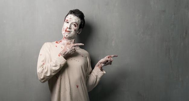 Zombie terrore che indica il laterale. vacanze di halloween