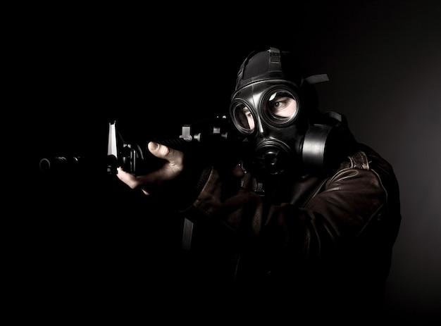 Terrorista con maschera antigas su oscurità